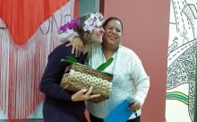 Two women hug while one holds a basket with a flower.
