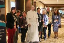 Attendees at the 2019 convening stand next to a image of Pope Francis.