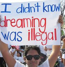 "A person holding up a sign that reads ""I didn't know dreaming was illegal."""