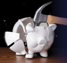 A hammer breaking a piggy bank.