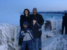 A family of four stands in front of Niagara Falls.