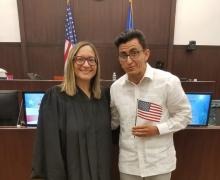 An immigration judge and new citizen holding an American flag in an immigration courtroom.