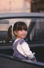 A young girl smiles at the camera from the back of a pickup truck.