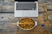 A plate of food in front of a laptop.